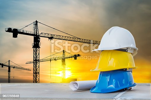 istock The white safety helmet at construction site with sunset silhouette and crane background 962255648