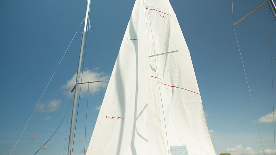 The white sail of an expensive sports yacht flutters against the blue sky in the port in sunny weather. High quality 4k footage