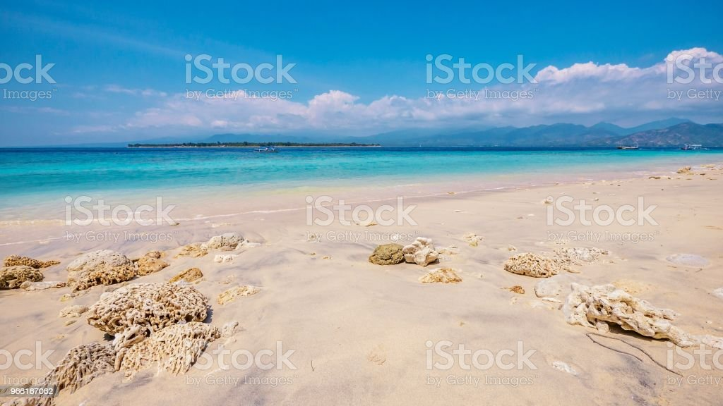 The white sand beach of Gili Meno Island in Indonesia at low tide, with its fine sand and some exposed hard coral visible. Turquoise water, Gili Air and Lombok islands are in the background. - Foto stock royalty-free di Acqua