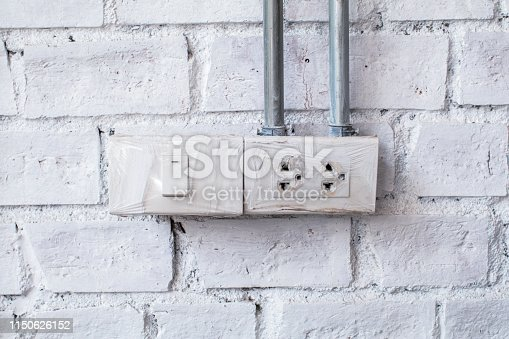 905087856istockphoto The white socket and switch on a brick wall. the use of electricity. Wall in a room with a plastic outlet 1150626152