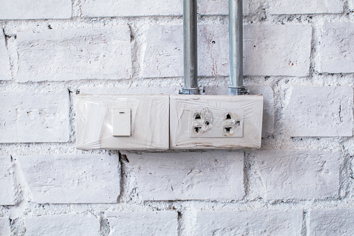 905087856 istock photo The white socket and switch on a brick wall. the use of electricity. Wall in a room with a plastic outlet 1150626152