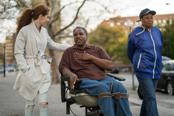 The White teenager girl talking with disabled wheel-chaired African American man and woman when they walking on the street together stock photo