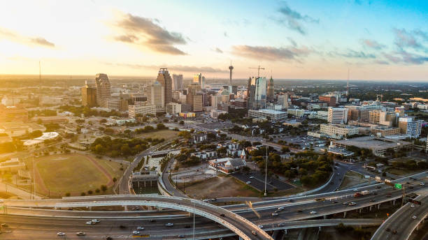 The whole city of San Antonio taken from a drone while its sunrise The image incompasses the whole city of San Antonio, including all of its landmarks and highways, and has a sun flare from the left while contrasting is a blue front from the right san antonio texas stock pictures, royalty-free photos & images