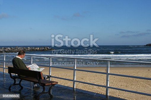 San Sebastian, Spain-October 31, 2007. The wide sandy beach in San Sebastian, Spain. An elderly man sitting on a bench on the waterfront next to the beach and reading a newspaper. Yellow sand and blue sky.