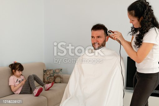 The wife cuts the hair of the man who cannot go to the barber because of the epidemic.