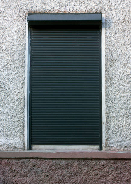 The window is covered with dark protective shutters on a gray wall. Security concept, property protection stock photo