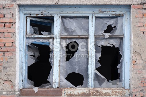istock the window of a brick house with broken glass. 1311221319