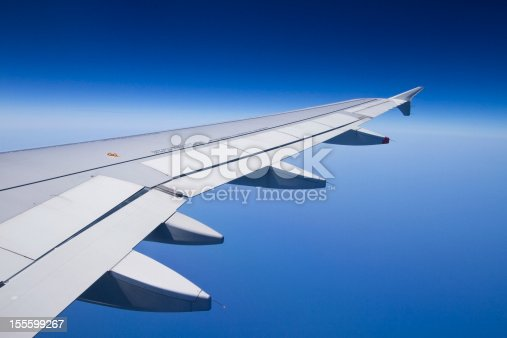 istock The wing of an airplane with a clear blue sky 155599267
