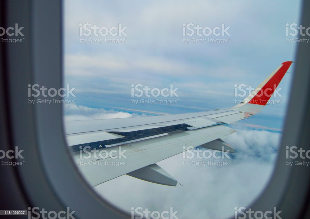 The wing of the aircraft flying above the clouds, seen through the...