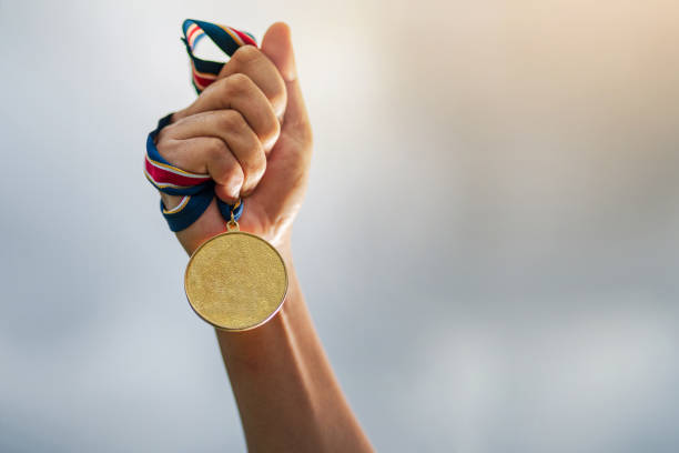 The winner and successful concept Hand holding gold medal on sky background, The winner and successful concept medal stock pictures, royalty-free photos & images