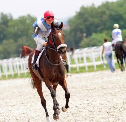 Action shot of jockeys in horse race.