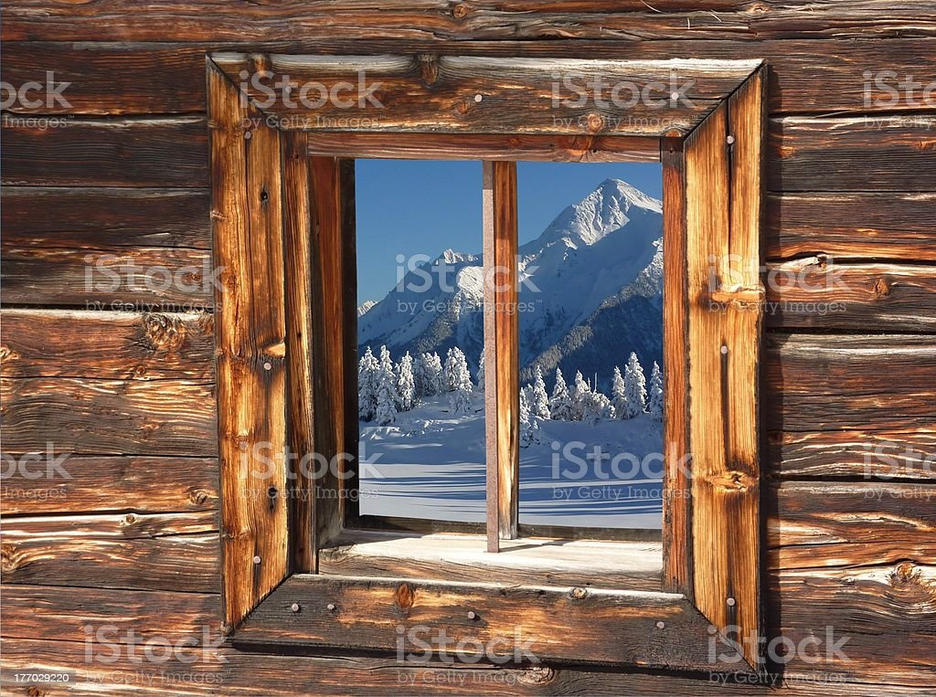 The wintry Alps in a wood window stock photo
