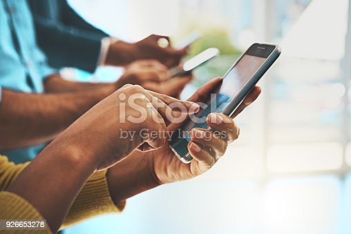 Cropped shot of unrecognizable businesspeople using their cellphones in the office