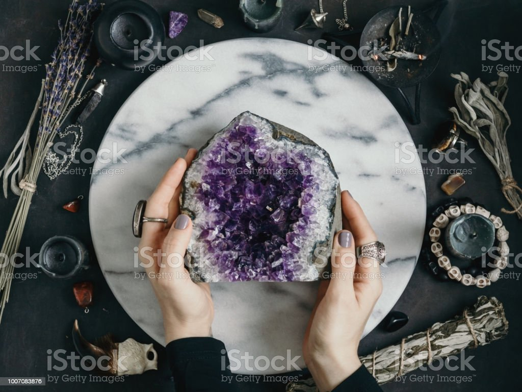 The witch is holding amethyst stone surrounded magic things. View from above. stock photo
