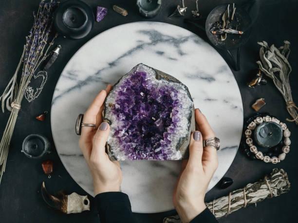 häxan håller ametist sten omgiven magiska saker. visa från ovan. - kristall bildbanksfoton och bilder