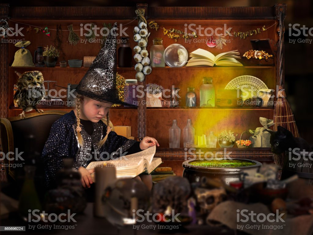 The wizard of room. Little girl in witch hat reads a big book of spells. Many mystical items. The concept of magic, Halloween stock photo