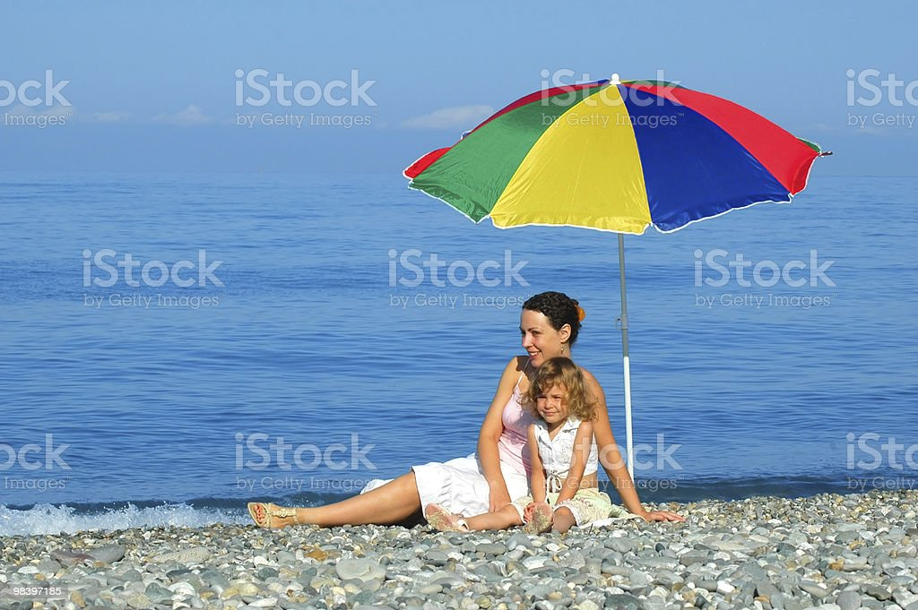 The woman and child sitting under an umbrella royalty-free stock photo