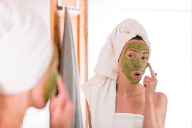 die frau gilt grün bio gesichtsmaske im badezimmer - makeup selbst gemacht stock-fotos und bilder