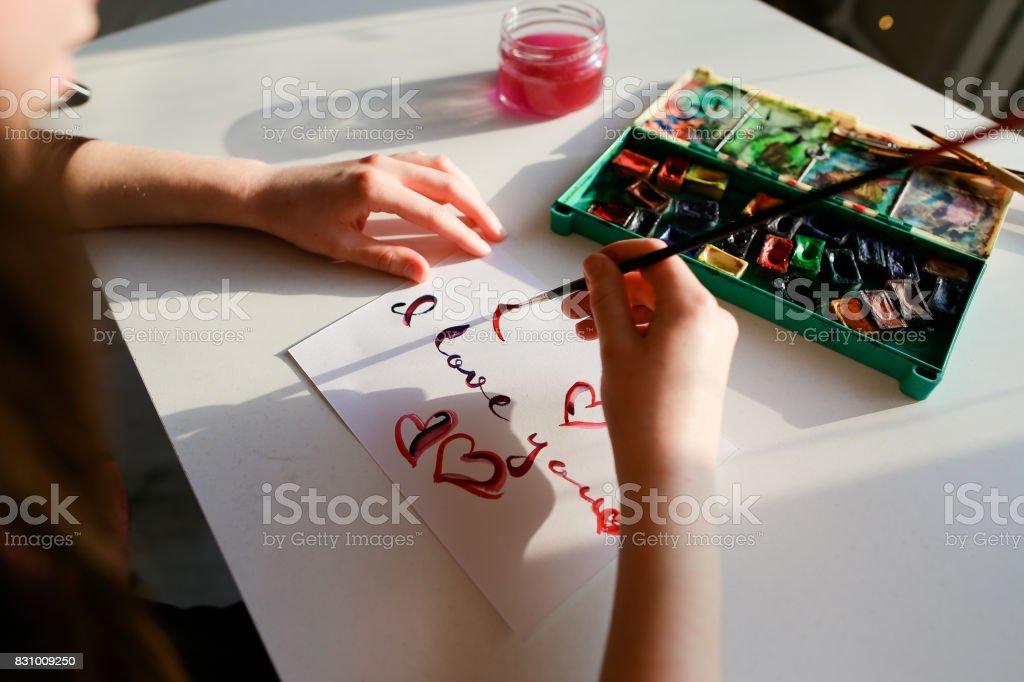 The woman artist in italics writes italic inscription on paper s stock photo