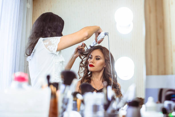 The woman at the hairdresser Hair stylist making ringlets to brunette woman. Hairdresser working with beautiful woman hair in hairdressing salon. saloon stock pictures, royalty-free photos & images
