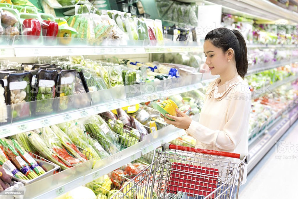 The woman attentively considers vegetables in shop stock photo