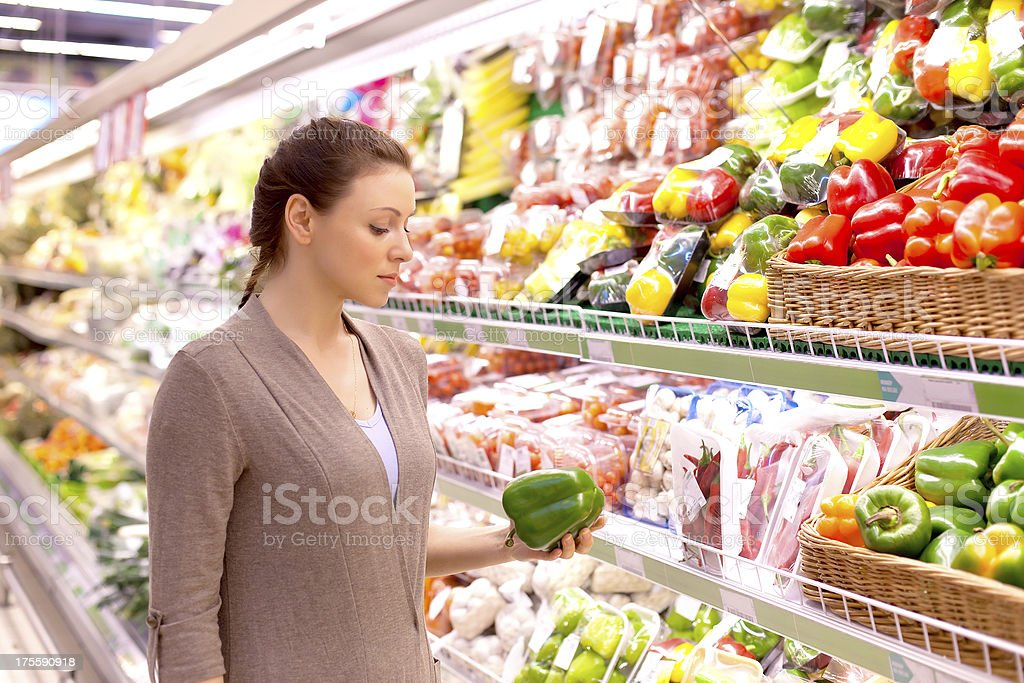 The woman attentively considers vegetables in shop royalty-free stock photo