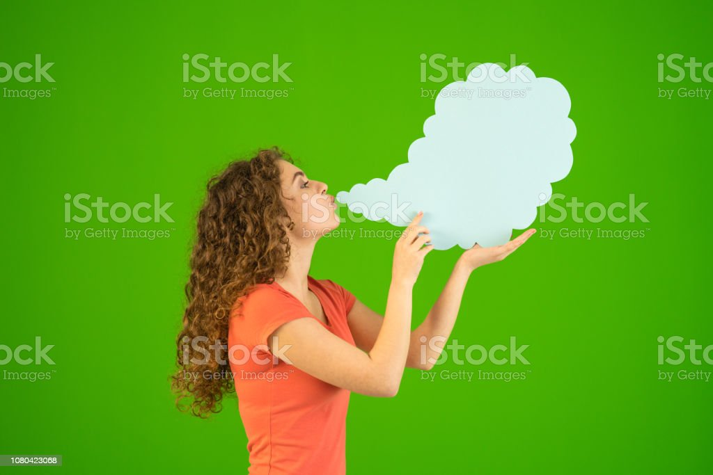 The woman blow a virtual smoke on the green background stock photo