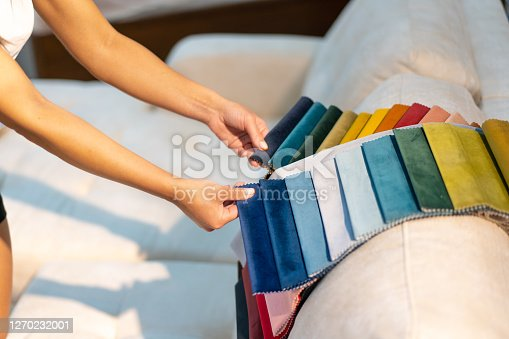 The woman chooses the fabric on the sofa. Textile industry background. Tissue catalog