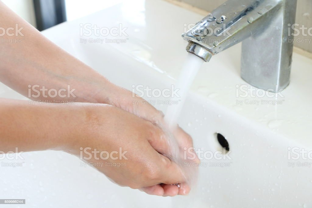 The woman cleaning dirty hands by washing hand with foam soap and water in white sink in bathroom stock photo