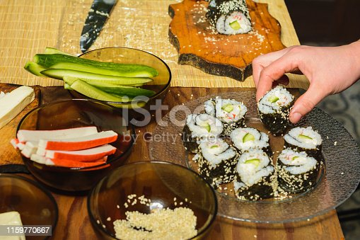 The woman cooked sushi and placed them on a round plate 2019