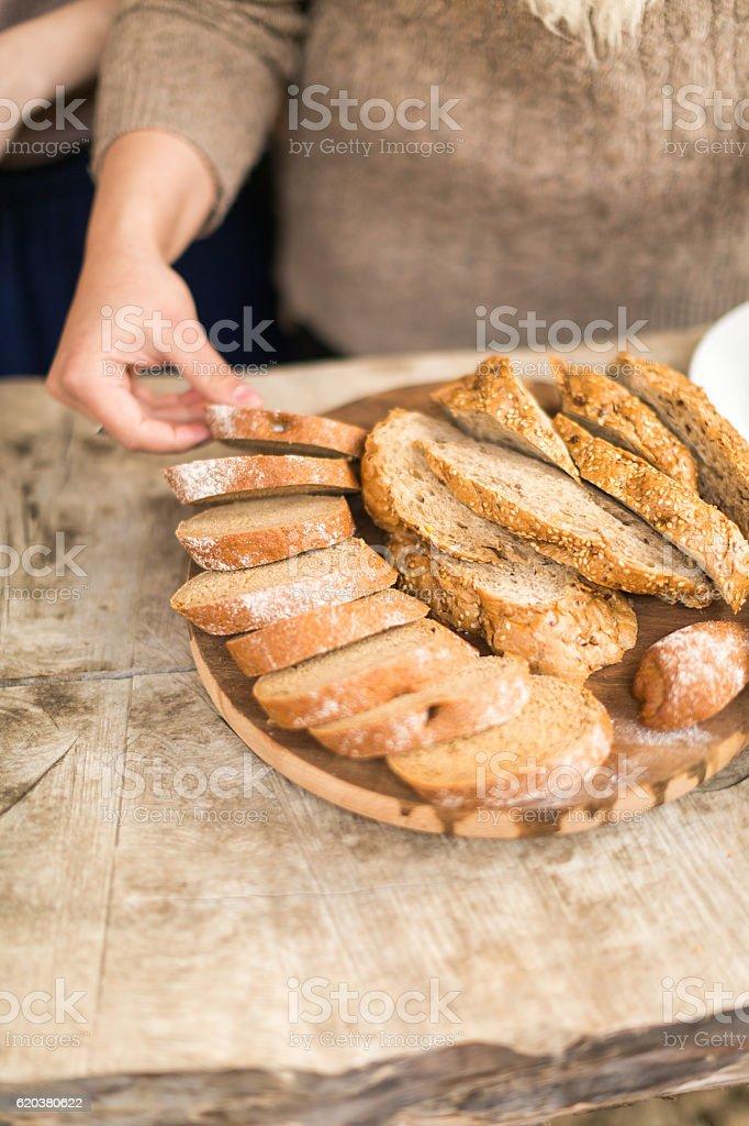 Kobieta cięcia chleba na drewnianym modułu. zbiór zdjęć royalty-free