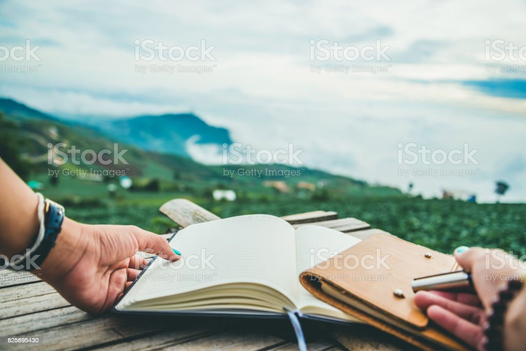 The woman hand holds the writings. Morning atmosphere The mountains are foggy. phetchabun phutubberg thailand stock photo
