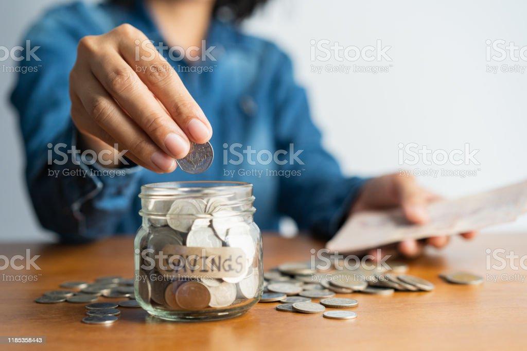 Kadın el bir cam şişe ve kahverengi ahşap bir masa, Yatırım iş, emeklilik, finans ve gelecekteki kavram için para tasarrufu üzerinde sikke bir yığın bir sikke koyarak. - Royalty-free Bankacılık Stok görsel