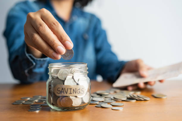 de vrouw hand zet een munt in een glazen fles en een stapel munten op een bruine houten tafel, investeringsbedrijf, pensioen, financiën en geld besparen voor toekomstig concept. - investering stockfoto's en -beelden