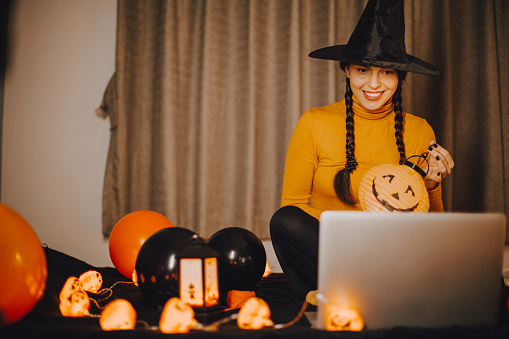 The woman has a video call for Halloween on her laptop