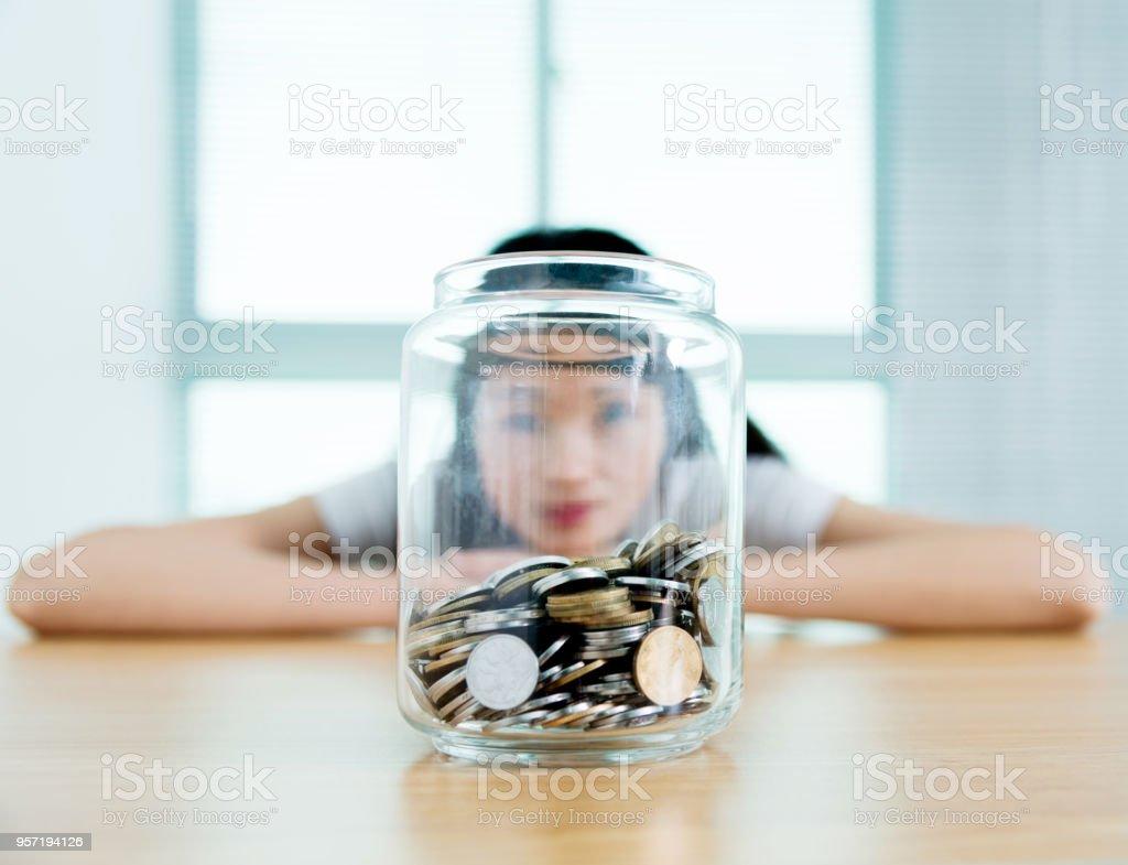 Die Frau versteckte sich hinter einem Glas voller Münzen – Foto