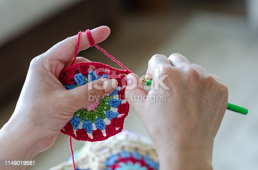 Senior woman is  knitting crochet. Hobby crafts things. Top view. Horizontal composition