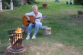 The woman is happy about the nice evening and plays on the guitar