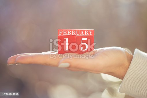 istock the woman is holding a red wooden calendar. Red wooden cube shape calendar for FEBRUARY 15 with hand 925046834