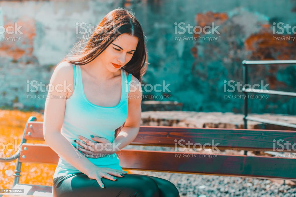 The woman is holding her belly. stock photo