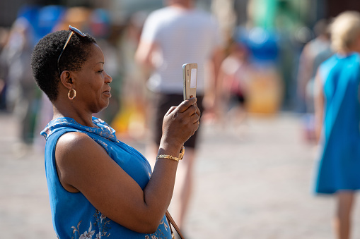 The woman is taking pictures with the phone.