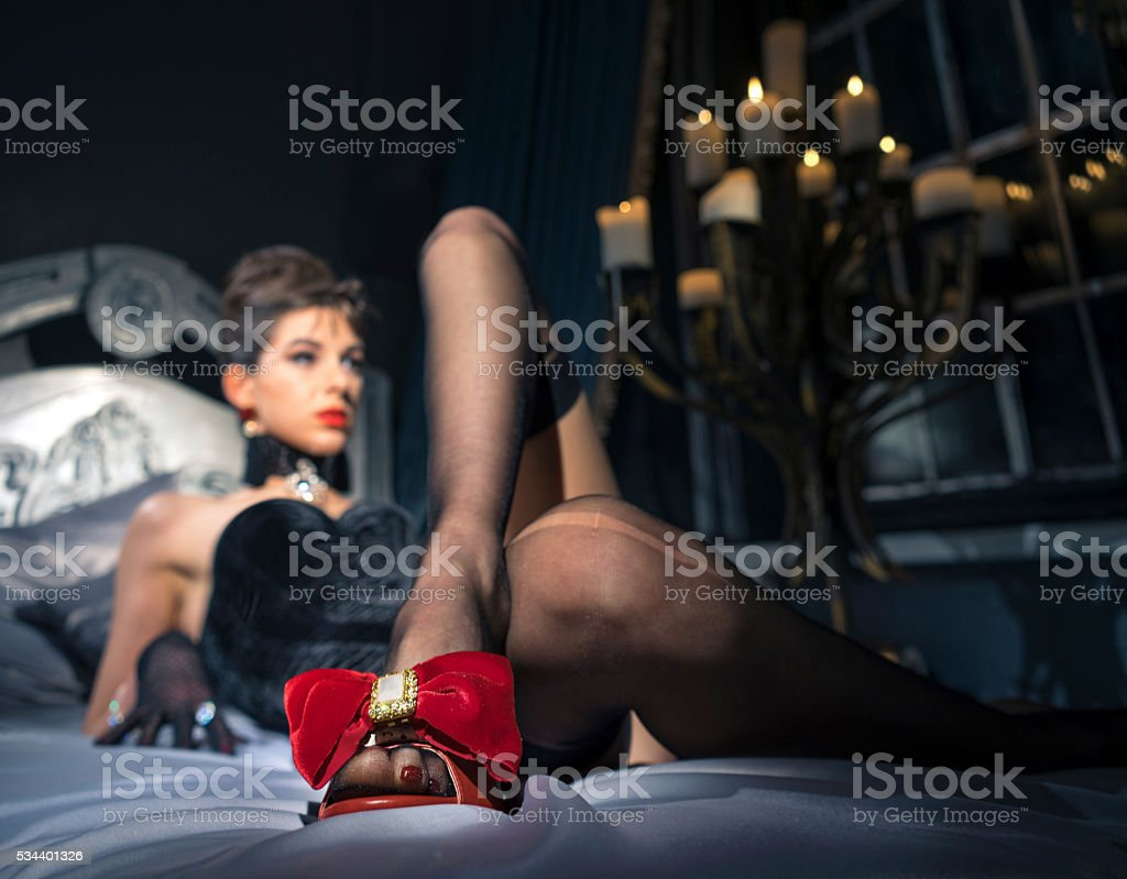 The woman lies on a bed in beautiful red sandals. stock photo
