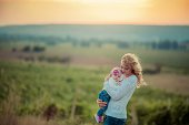 The woman mom with a young child outdoors in the beautiful mountains blurred in the background