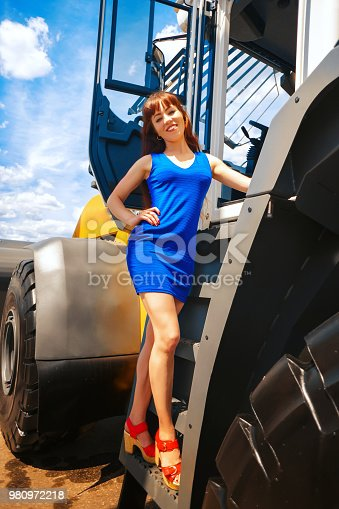 attractive young woman posing next to tractor