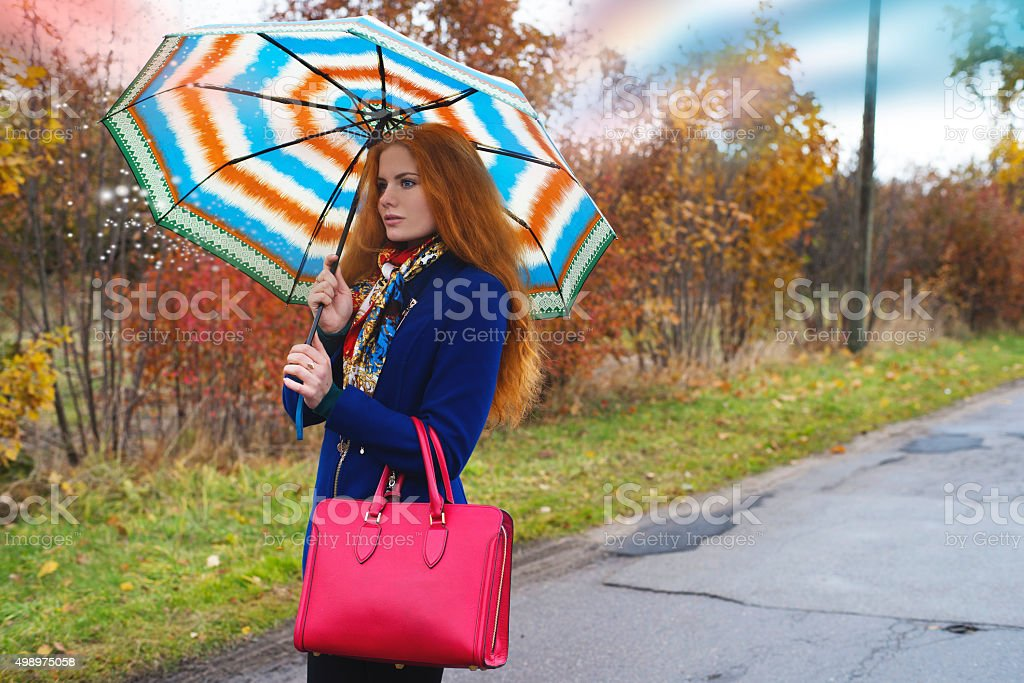 The woman on the road with an umbrella stock photo