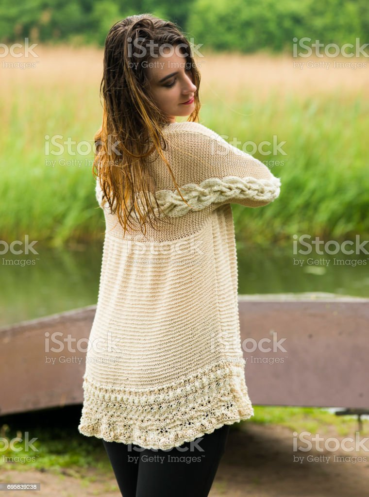 The woman outdoors, enjoys a drizzle and meditates stock photo