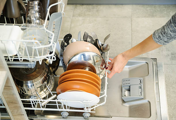 The woman pushed the dirty dishes in the dishwasher. – Foto