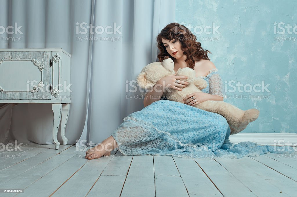 The woman put her hands on the bear toy. stock photo