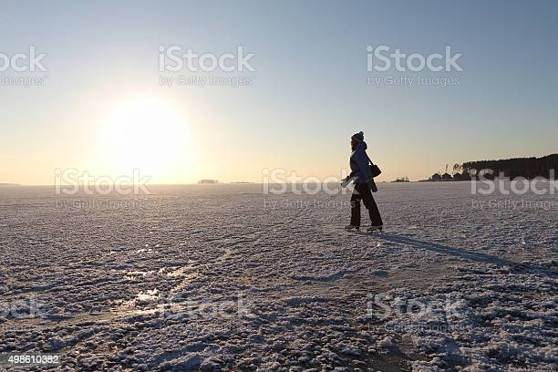 Photo of The woman skating on the frozen river at sunset