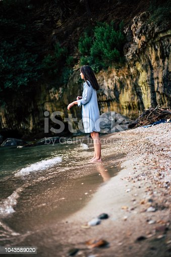 istock The woman stands on the coast next to the rock 1043589020
